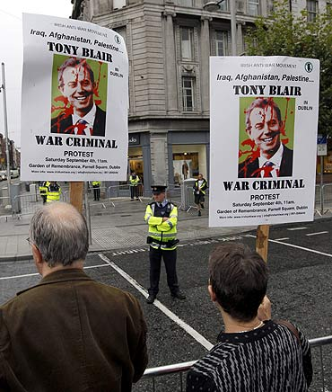 Protesters, chanting slogans against former British prime minister Tony Blair, stand outside a bookshop in Dublin, Ireland