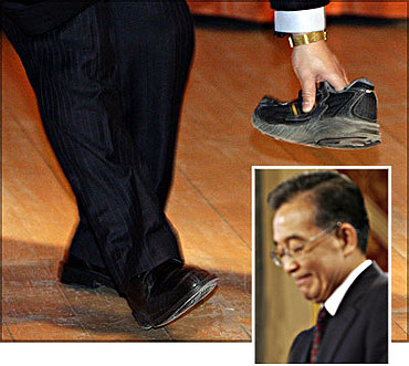 A security guard picks up a shoe that was thrown towards Chinese Premier Wen Jiabao (inset) at the University of Cambridge.