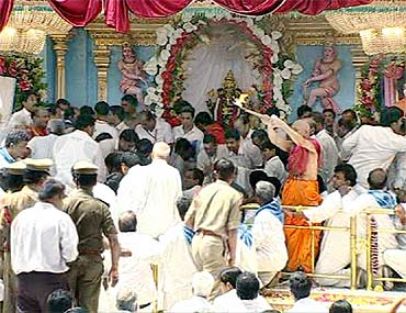 Devotees lower the body of Sathya Sai Baba at the Kumawant Hall in Puttaparthy on Wednesday