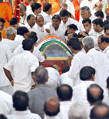 Devotees carry the body of Sathya Sai Baba during his funeral