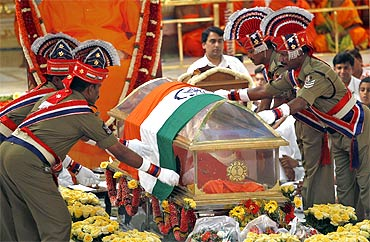 Police personnel place a national tricolour on a glass box containing Sai Baba's body as a mark of respect during his funeral