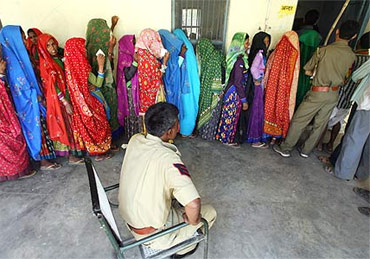 Voters wait to cast their votes at a polling booth