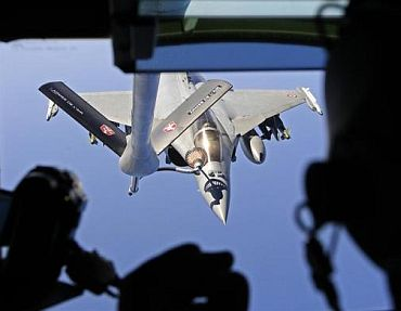 A French Rafale fighter jet refuels with an airborne Boeing C-135 refuelling tanker aircraft from the Istres military air base during a refuelling operation above the Mediterranean Sea