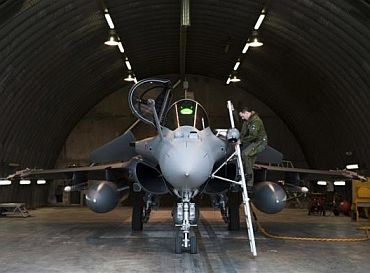 A pilot boards his French Dassault Rafale combat aircraft, seen in this photo released by ECPAD (French Defence communication and audiovisual production agency), at the Saint-Dizier military base, eastern France
