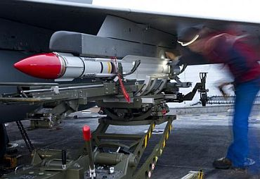 In this photo released March 24, 2011 by the French Defence communication and audiovisual production agency, a French Navy ordnance crew member loads a Mica missile under the wing of a Rafale fighter jet
