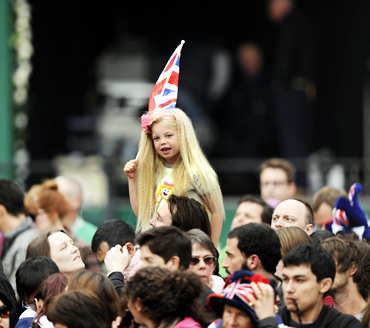 A girl with a British flag smiles among people gathered outside Buckingham Palace before the wedding of Britain's Prince William and Kate Middleton at Westminister Abbey.