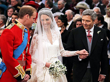 Prince William stands at the altar with his bride, Kate Middleton, and her father Michael, during their wedding ceremony