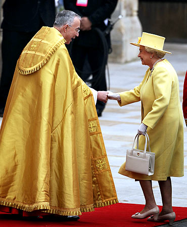 Queen Elizabeth II greets The Right Reverend Dr John Hall, Dean of Westminster as she arrives to attend the royal wedding at Westminster Abbey