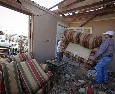 Ashla Sullivan (Left) removes a couch from her destroyed house in the aftermath of deadly tornados in Tuscaloosa, Alabama