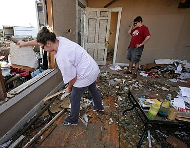 Ashla Sullivan throws out debris from her destroyed house as her husband, Adam Sullivan, talks on the phone