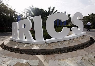 A man walks past a signage decoration for the BRICS summit outside Sheraton Hotel, the venue for the third BRICS summit in Sanya, Hainan province