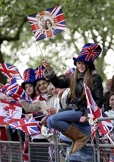 A royal supporter waves a Union Jack as she waits along the Procession Route in London