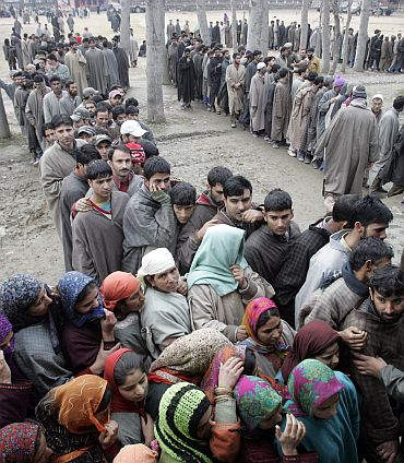 People wait in line to cast their vote during a local election in Kashmir