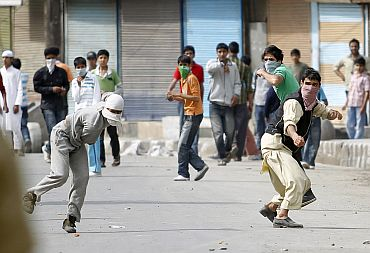 Kashmiri protestors throw stones towards security personnel during an agitation in Srinagar