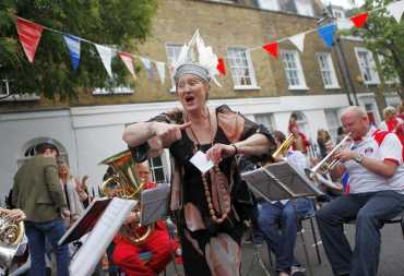 Resident and former opera singer Dame Ann Evans sings as the brass band plays Rule Britannia during a street party to celebrate the royal wedding