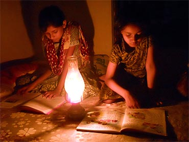 Girls use latern to light up their house in a Bihar village