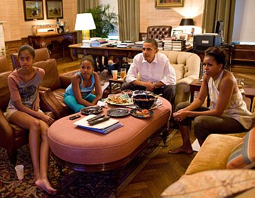 President Barack Obama, First Lady Michelle Obama, and their daughters Sasha and Malia watch the World Cup soccer game between the US and Japan, from the Treaty Room office in the residence of the White House