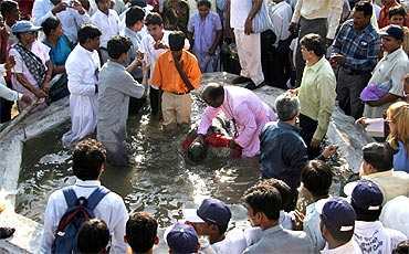A priest baptises a student during a mass conversion ceremony in Nagpur