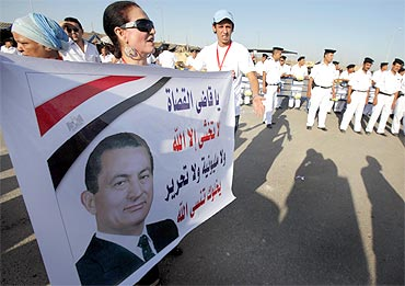A supporter of former Egypt president Hosni Mubarak holds a poster of him outside the police academy