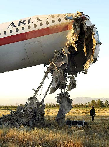 An official stands beside the wreckage of a passenger airplane in Mashhad, Iran, on July 24, 2009. 17 were killed when the aircraft caught fire while landing at the airport of Mashhad