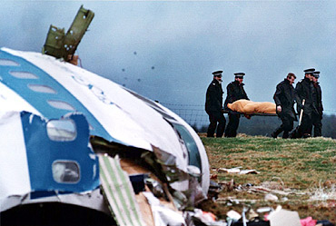 File photo shows rescue personnel carrying a body away from the site of the Lockerbie