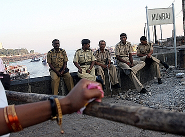 Policemen relax near the Gateway of India in Mumbai