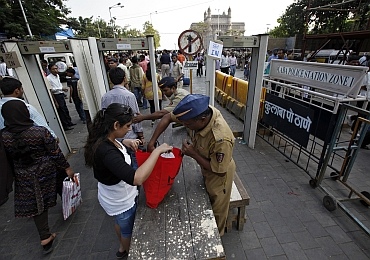 A policeman checks a visitor's bag at a security checkpoint at the entrance of the Gateway of India