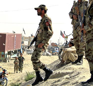 Paramilitary soldiers stand guard along a road near the Afghanistan border