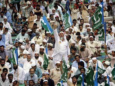 Supporters of Jamaat-e-Islami shout slogans against drone attacks in Karachi