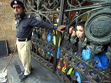 Children watch an anti-America rally from behind the closed gate of a market in Karachi