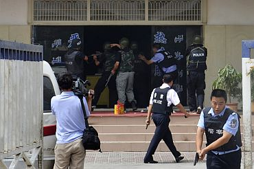 Armed Chinese policemen trying to rescue hostages at a police station during a clash at Hotan in Xinjiang Uygur Autonomous Region.