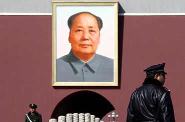 Paramilitary policemen stand guard in front of the portrait of Mao in Tiananmen Square in Beijing