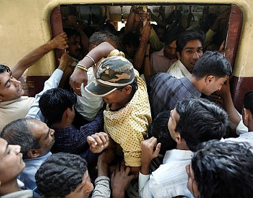 Commuters make their way into a crowded compartment of a suburban train in Mumbai