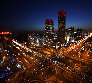 Vehicles drive on Three Ring Road (left) and Jianwai Street (right) during the evening rush hour in central Beijing