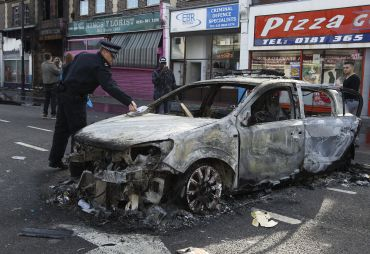 A police officer removes identification from a police car set alight and burned during riots in Tottenham, north London.