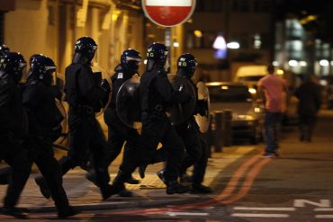 Police officers wearing riot gear run along a street in Tottenham, north London
