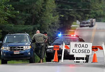 Law enforcement officers set up a road block as investigations continue near the scene of a shooting in Copley, Ohio