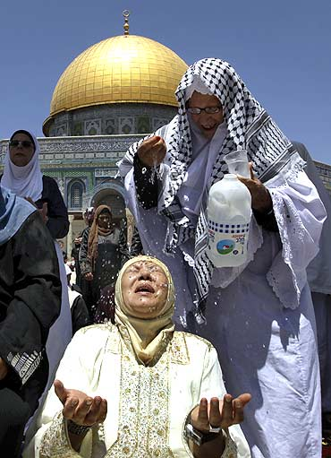 A Muslim woman tries to cool down with water in front of the Dome of the Rock on the compound known to Muslims as al-Haram al-Sharif and to Jews as Temple Mount in Jerusalem's Old City