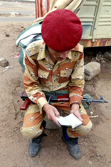 A defected soldier who has joined sides with anti-regime protesters to demand the ouster of Yemen's President Ali Abdullah Saleh, reads a Koran at a checkpoint in Taghyeer (Change) Square in Sanaa