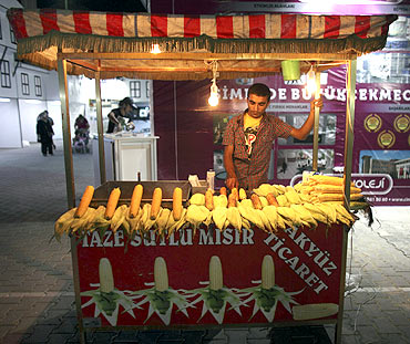 A vendor, selling corn, waits for customers after iftar in Beylikduzu, a district of Istanbul