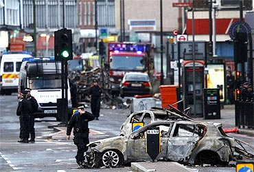 Police officers investigate after riots in Tottenham in north London