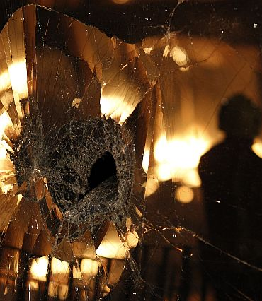 A firefighter is reflected in a damaged window in Tottenham, north London