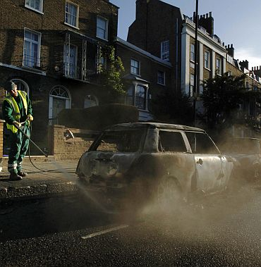 A street cleaner hoses down the street around burned out mini cars set alight during riots in Hackney in London