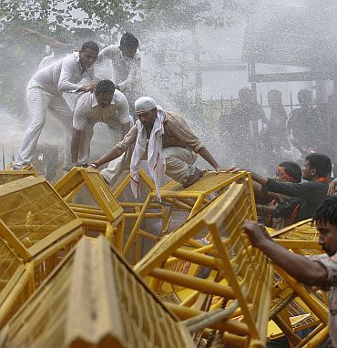 Police spray demonstrators from the India's main opposition Bharatiya Janata Party with water canons as they try to remove barricades during the anti-government march