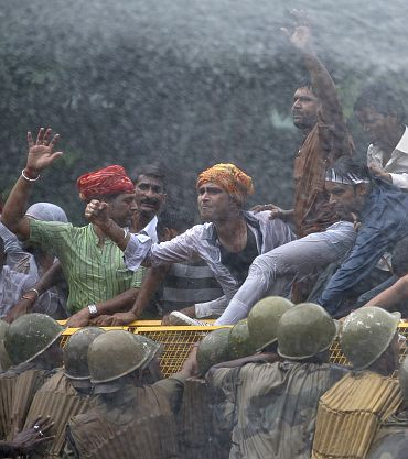 Police spray demonstrators with water canons