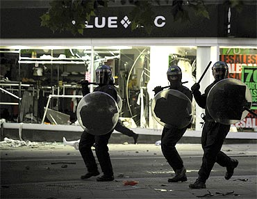 Riot police charge past a looted shop on Peckham High Street in south London on Monday night.