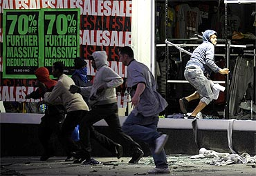 Looters run from a clothing store in Peckham, London on Monday night