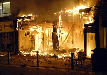 A fierce blaze guts a store after looters rampaged through a shopping mall in Woolwich, southeast London