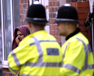 A woman reacts at the scene where three men were killed by a car in Winson Green area of Birmingham, central England