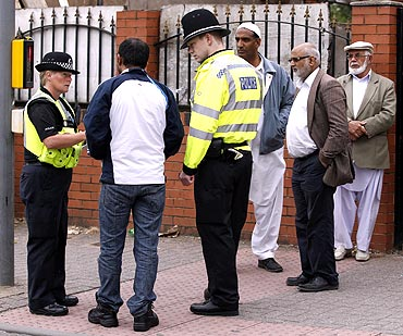 Police officers speak to men at Winson Green area of Birmingham, central England